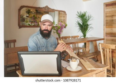 Hipster in cap watching laptop and eating delicious snack with coffee in cozy cafeteria.