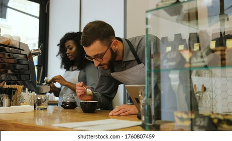 Hipster caucasian barista with beard and african young woman working in modern trendy coffee shop cafe, woman washing cup and man sniffing the fresh coffee.