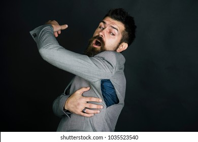Hipster chose small size jacket, seam torn under armpit. Man with beard wears jacket with hole on dark background. Bad quality of clothes concept. Surprised guy bought counterfeit or fake brand.