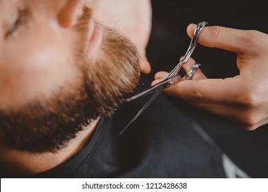 Hipster client man visiting in barber shop shaving beard