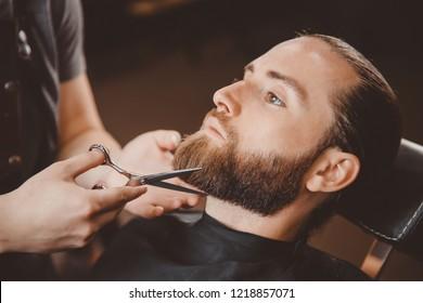 Hipster client man visiting in barber shop shaving beard scissors