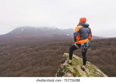 Hipster - a climber in a down jacket and a knitted cap stand and rests on the top of a rock