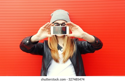 Hipster cool girl taking picture on smartphone self-portrait, screen view, over red background