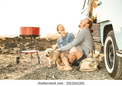 Hipster couple with cute dog traveling together on oldtimer mini van transport - Travel lifetstyle concept with indie people on minivan adventure trip having fun in barbecue moment - Warm retro filter