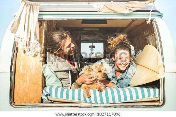 Hipster-Paar mit süßem Hund, der zusammen auf dem Mini-Kleintransporter fährt - Lebensinspirierungskonzept mit Hippie-Leuten auf Mini-Abenteuerreise im Relax-Moment - Hellwarmer Retro-Filter