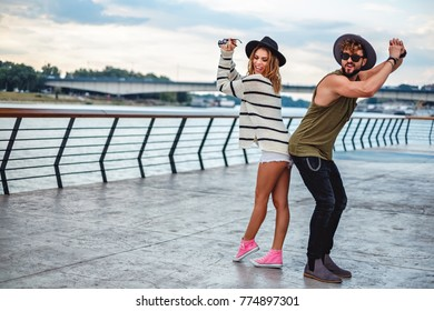 Hipster couple dancing and having fun by the river