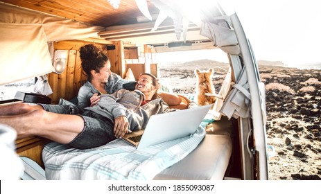 Hipster couple with dog traveling together on retro mini van transport - Digital nomad concept with indie people on minivan romantic trip working at laptop pc in relax moment - Warm contrast filter