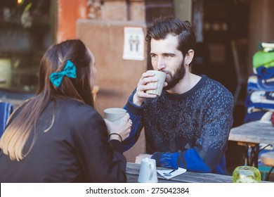 Hipster couple drinking coffee in Stockholm old town. They're sitting face to face. The man is wearing a blue sweater and the woman a striped shirt with black leather jacket.