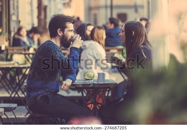 ストックホルムの古い町でコーヒーを飲むヒップスター夫婦。彼らは向かい合って座っている。その男は青いセーターを着て、女は黒い革のジャケットを着た縞のシャツを着ている。シースルーショット。