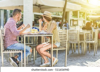 Hipster couple eating street food and toasting beer outdoor. Young cheerful people having fun in vacation holidays - Love and relationship concept - Focus on girl face - Warm filter with sun flare