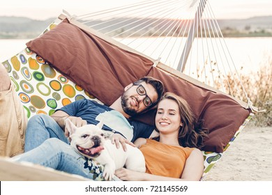 Hipster couple on a trip to the beach, young freelancer man relaxing in a hammock with his woman, romantic couple on vacation with bulldog pet