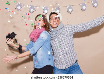 Hipster couple in a Photo Booth party with blowing colorful confetti and taking selfie