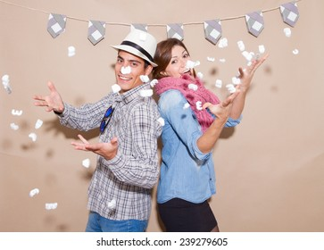 Hipster couple in a Photo Booth party with blowing confetti