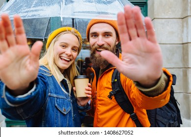 """Hipster couple traveler under transparent umbrella in bright casual clothes saluting you, saying """"Hi"""" in city street Positive beard man and blonde woman drrinking hot coffee.. Lifestyle love concept."""