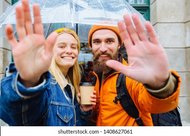 "Hipster couple traveler under transparent umbrella in bright casual clothes saluting you, saying ""Hi"" in city street Positive beard man and blonde woman drrinking hot coffee.. Lifestyle love concept."