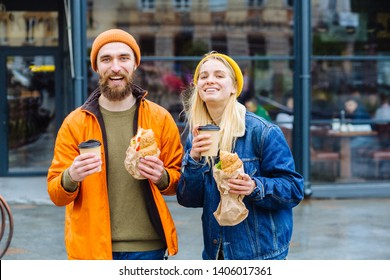 Hipster couple of young lovers. Teenager girl and her beard boyfriend walking on the street, eating street food, drinking coffee and looking at camers, giving sincere smiles.