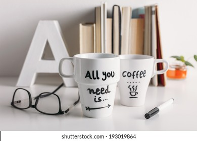Hipster cup of coffee on a books library./ Two white coffee mug with diy decoration.