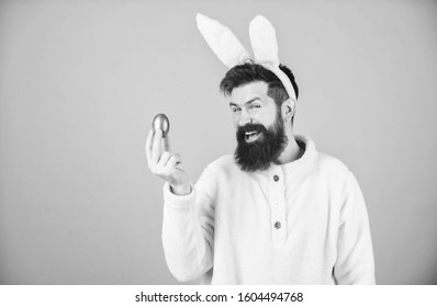 Hipster cute bunny long ears blue background. Easter bunny. Having fun. Funny bunny with beard and mustache hold pink egg. Bearded man wear silly bunny ears. Easter symbol concept. My precious.