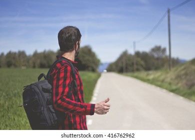 hipster doing hitchhiking in the road