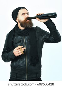 hipster drink from bottle and smoking cigar in black leather jacket, hat and scarf isolated on white studio background