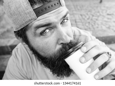 Hipster drink coffee to go while sit stairs outdoors. Urban food culture concept. Tasty sip concept. Tasty coffee tea in paper cup close up. Man bearded hipster enjoy drink paper cup urban background.