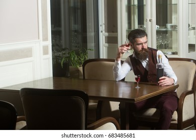 Hipster drinking wine served with two glasses. Sad man with long beard in brown vest sitting alone in restaurant. Bottle at table. Alcohol and appetizer. Unhealthy lifestyle and bad habits