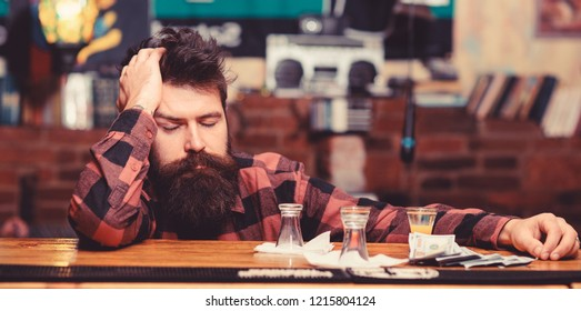 Hipster fall asleep near alcoholic drink, short cocktail. Man with tired face sit alone at bar counter, put head on table. Overdrink concept. Guy spend leisure in bar, defocused background.