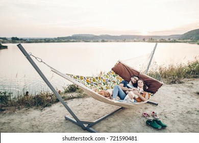 Hipster family on vacation concept, happy woman and man relaxing on a hammock at the beach with their cute bulldog pet, couple lying near a lake at sunset