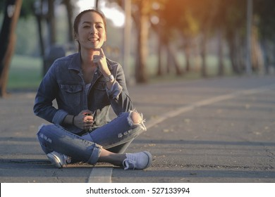 hipster fashion girl in jeans sitting on the road in garden with smile happy in sunset light
