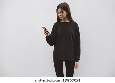 Hipster female holding in her hand a modern smartphone standing on the background of a white wall. Blank hoodie with empty place for logo, text or design. Black blank sweatshirt mockup