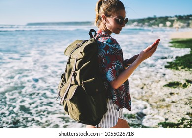 Hipster female lover of trips with travel rucksack exploring new tropical places during summer adventure on island while reading message on smartphone walking along coastline washed by ocean water