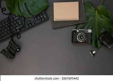 Hipster flatlay with camera, keyboard, lens, monstera leaves, notebook and binocular on grey table. Dark working space top view. Creative work table for photographer, traveller, blogger