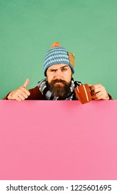 Hipster with flirty face holds tea or coffee cup and shows thumbs up. Man in warm hat holds cup on green and pink copy space background. October beverage idea. Autumn and hot drink season concept