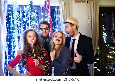 Hipster friends celebrating New Years Eve together, photobooth p