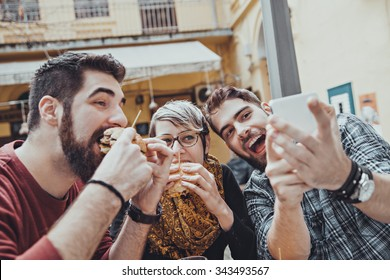 Hipster Friends In Fast Food Restaurant Taking Selfie While They Are Eating Burgers