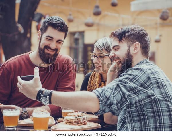 Hipster Friends In Fast Food Restaurant Taking Selfie