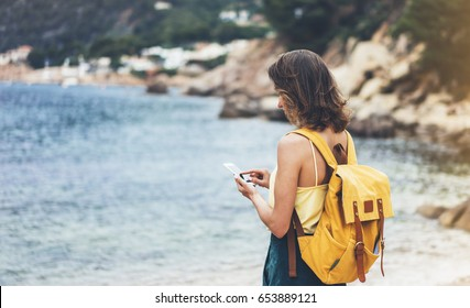 Hipster girl with backpack hold on smart phone gadget in sand coastline, mock up. Traveler using in female hand mobile on background beach seascape. Tourist look on blue sun ocean, summer lifestyle