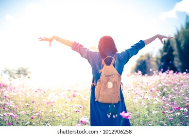 Hipster girl with backpack on beautiful cosmos field flower and blue sky cloudy.