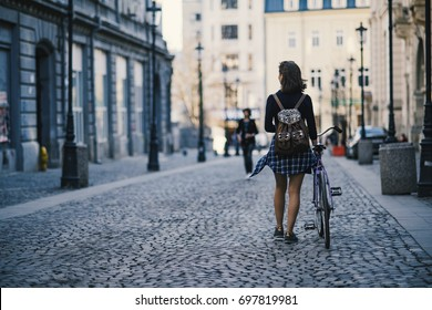 Hipster girl with a bike walking on the street