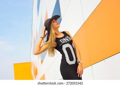 Hipster girl in a black dress with the number one in a vintage hat emotionally posing near multicolor wall