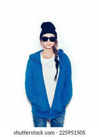 Hipster girl in blue hoodie and black beanie against white background, not isolated