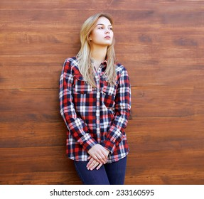 Hipster girl in checkered shirt posing against the wooden background outdoors