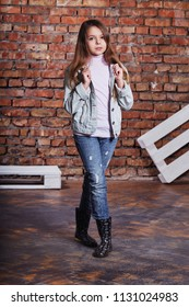 Hipster girl child wearing denim jacket,jeans posing against rough brick wall, minimalist urban clothing style. Full-length kid teenager model in stylish casual clothes.