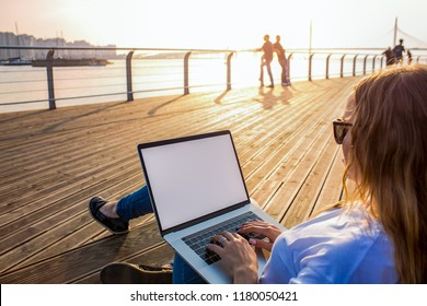 Hipster girl distance working on laptop computer with mockup empty screen with copy space for advertising content while relaxing on seafront in sunny summer day. Blogger keyboarding on blank netbook