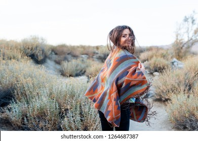 Hipster girl in gypsy look, young traveler in the desert nature in Coachella Valley, California, USA.