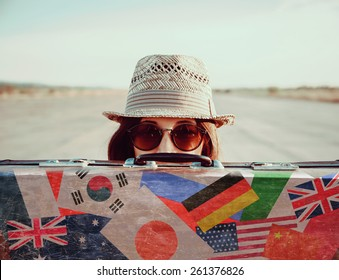 Hipster girl in a hat and sunglasses looks out from vintage suitcase. Suitcase with stamps flags of different country