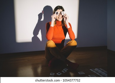 Hipster girl having fun with photo slides in front of projector screen. Young woman holding photo slides and smiling