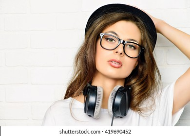 Hipster girl with headphones stands by a white brick wall.