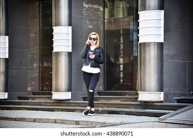hipster girl holding a cup of coffee and talking on cellphone