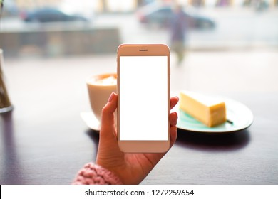 Hipster girl holding mobile phone with empty mockup copy space on the screen background for promotional content while sitting with cup of coffee and cake in restaurant. Female using smartphone